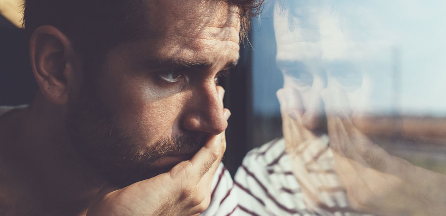 Man looks out the window with worried expression